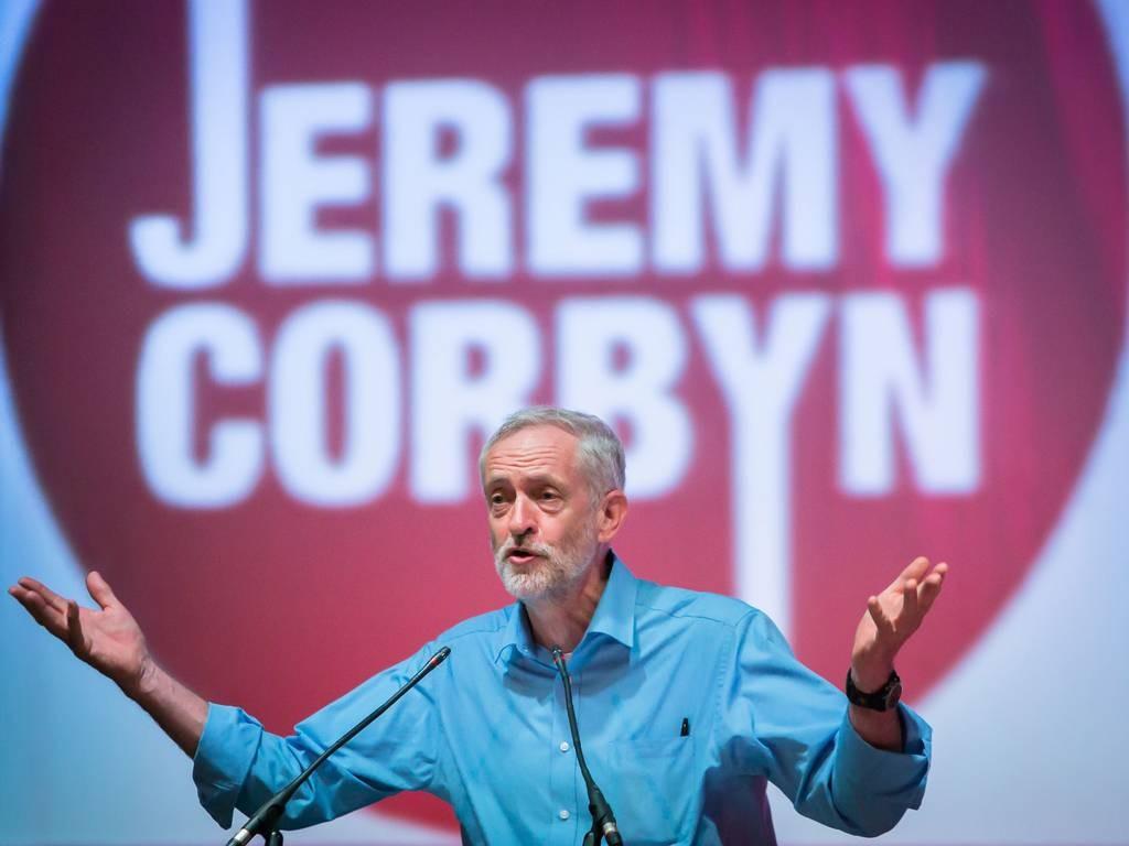 Jeremy Corbyn parla in pubblico, con il banner della sua campagna elettorale alle spalle
